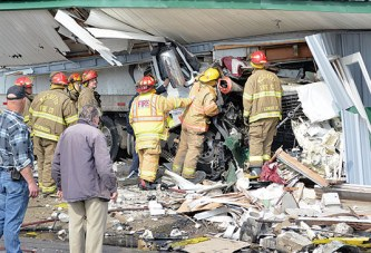Truck smashes through building