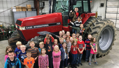 Hardin Northern first-graders pose around tractor after FFA lesson
